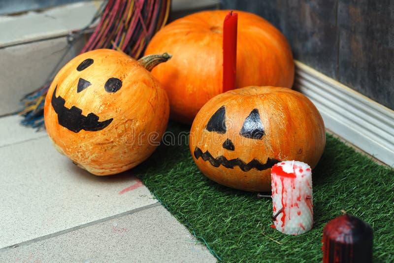 Composizione, fondo per Halloween Zucche dipinte, candele e un supporto della scopa all'entrata al pavimento fotografia stock
