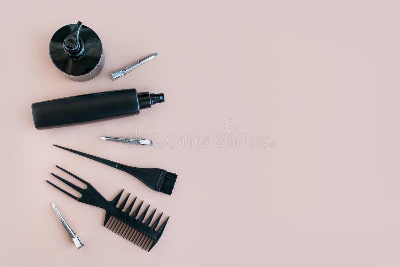 Composizione minima posta piano con gli strumenti del salone di capelli neri su fondo pastello fotografia stock