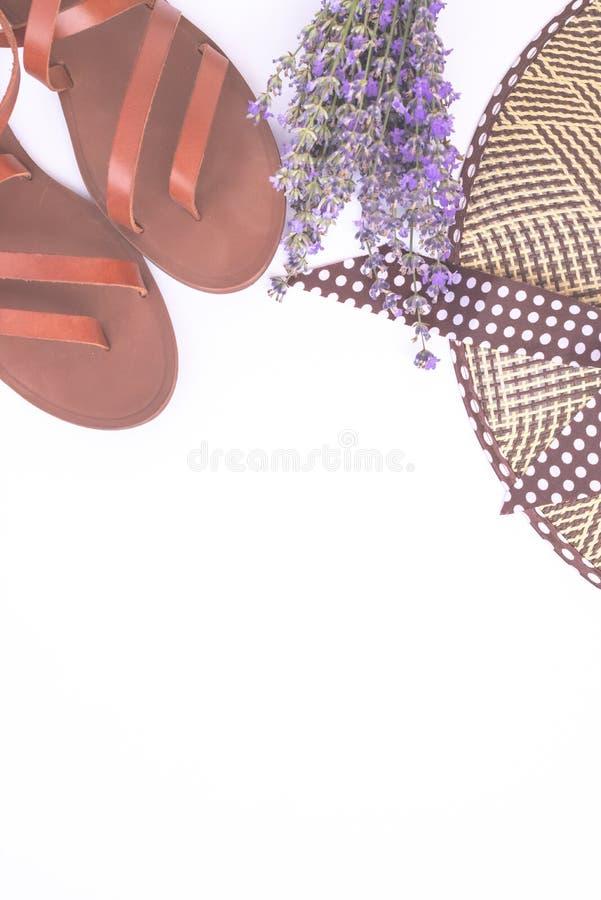 Composizione in modo di estate Mazzo di lavanda porpora, del cappello di paglia dell'estate delle donne e dei sandali di cuoio is immagine stock libera da diritti