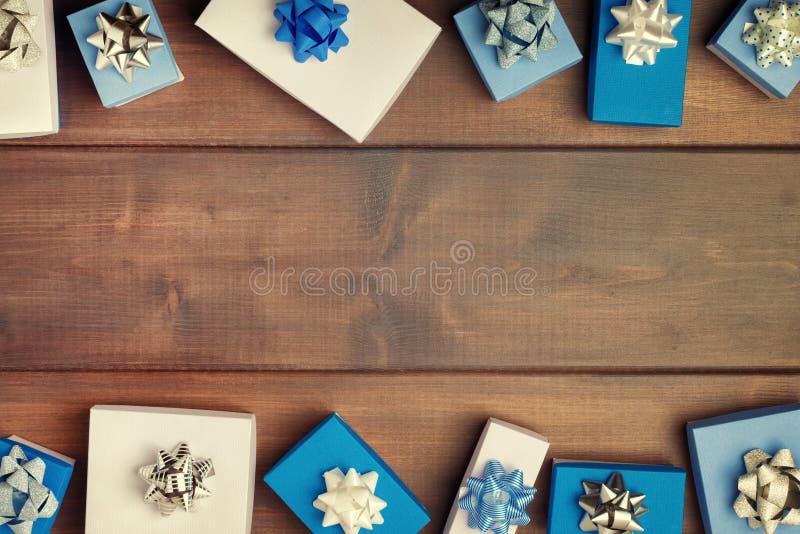 Composizione in Natale, bella struttura Piccoli contenitori di regalo blu e bianchi, con i bei archi d'argento Copi lo spazio fes immagini stock libere da diritti