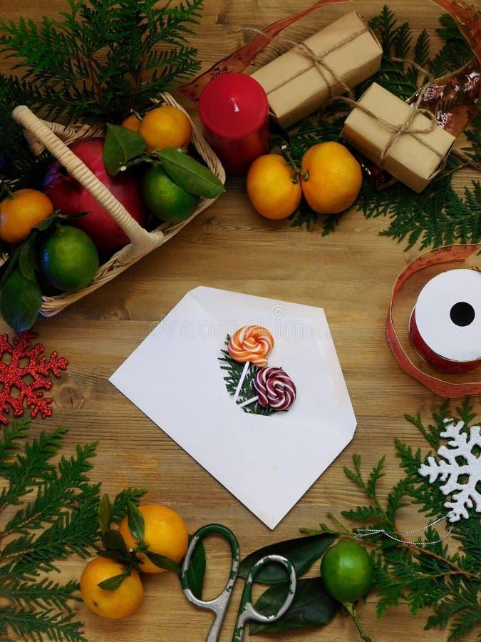 Composizione in Natale che consiste della busta con una sorpresa, un agrume, i dolci, i rami del thuja e le scatole attuali fotografia stock