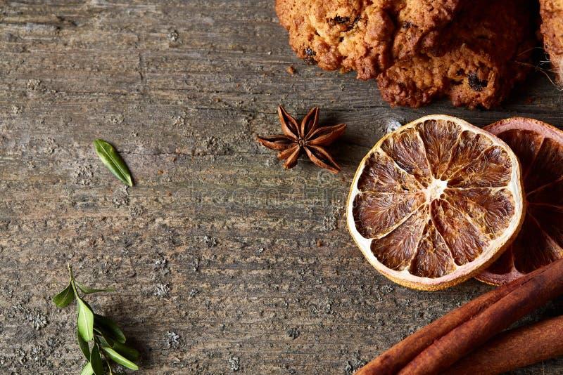 Composizione in Natale con i biscotti del cioccolato, la cannella e le arance secche su fondo di legno, primo piano immagine stock libera da diritti