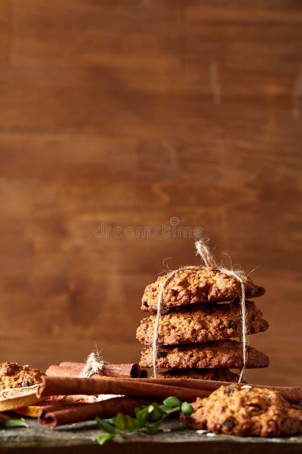Composizione in Natale con i biscotti del cioccolato, la cannella e le arance secche su fondo di legno, primo piano fotografia stock