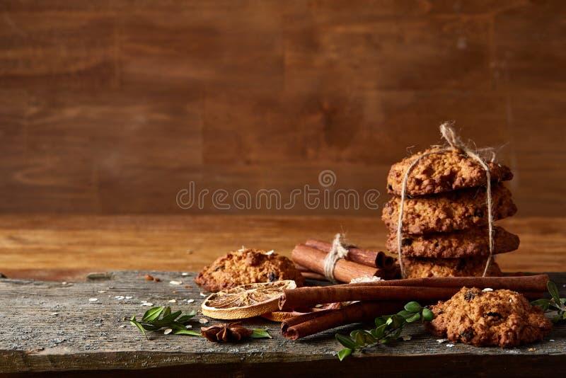Composizione in Natale con i biscotti del cioccolato, la cannella e le arance secche su fondo di legno, primo piano immagini stock