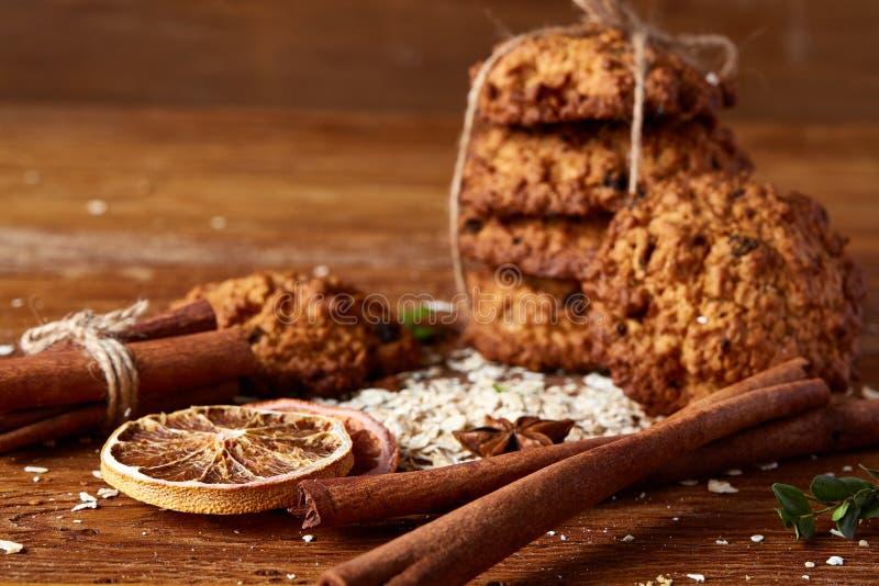Composizione in Natale con i biscotti del cioccolato, la cannella e le arance secche su fondo di legno, primo piano immagine stock