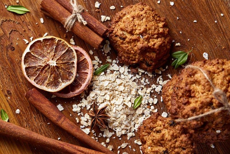 Composizione in Natale con i biscotti del cioccolato, la cannella e le arance secche su fondo di legno, primo piano fotografia stock libera da diritti