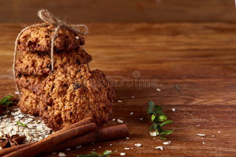 Composizione in Natale con i biscotti del cioccolato, la cannella e le arance secche su fondo di legno, primo piano immagini stock libere da diritti