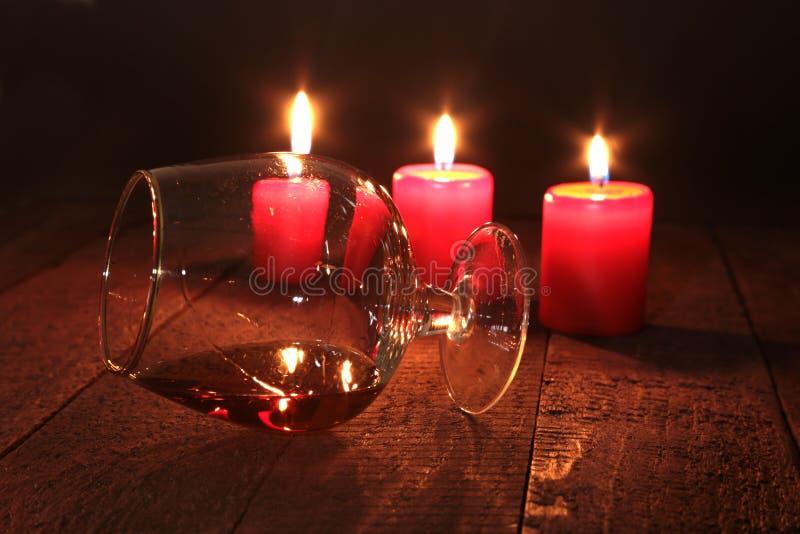 Composizione in Natale con il cognac, il contenitore di regalo e la candela di vetro sulla tavola di legno immagini stock libere da diritti