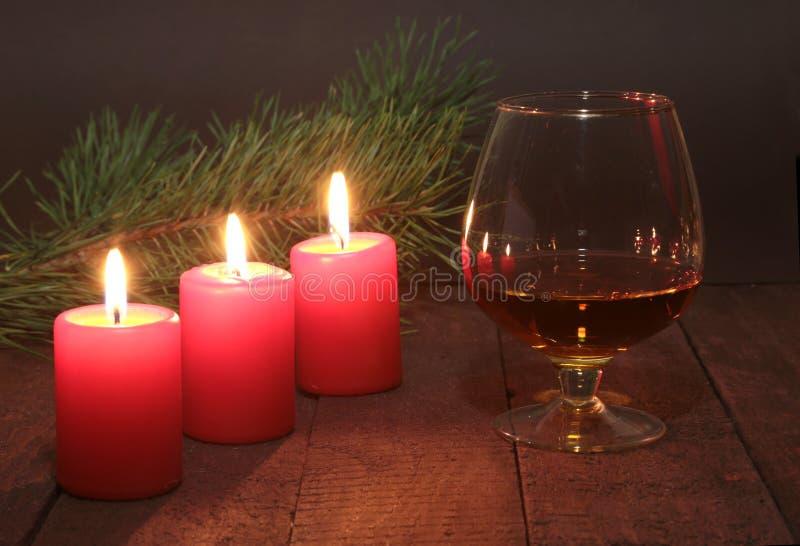 Composizione in Natale con il cognac, il contenitore di regalo e la candela di vetro sulla tavola di legno fotografia stock libera da diritti