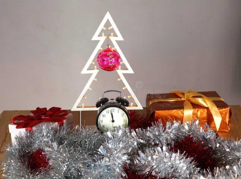Composizione in Natale con l'albero ed orologio sulla tavola immagini stock