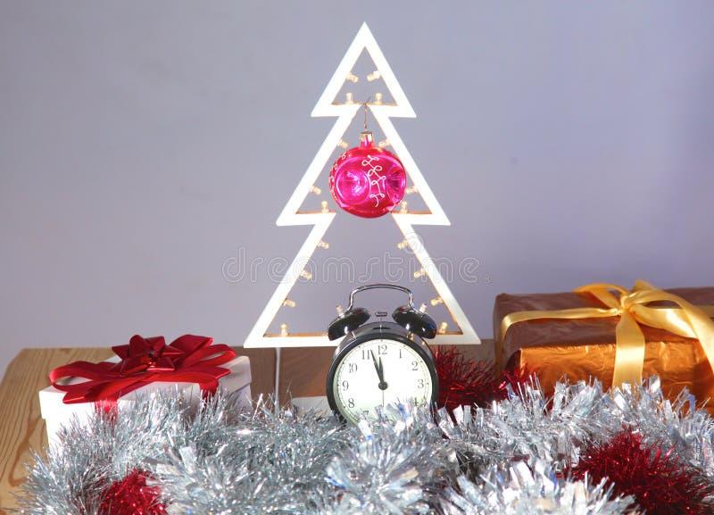 Composizione in Natale con l'albero ed orologio sulla tavola fotografie stock libere da diritti