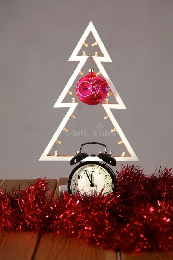 Composizione in Natale con l'albero ed orologio sulla tavola fotografia stock
