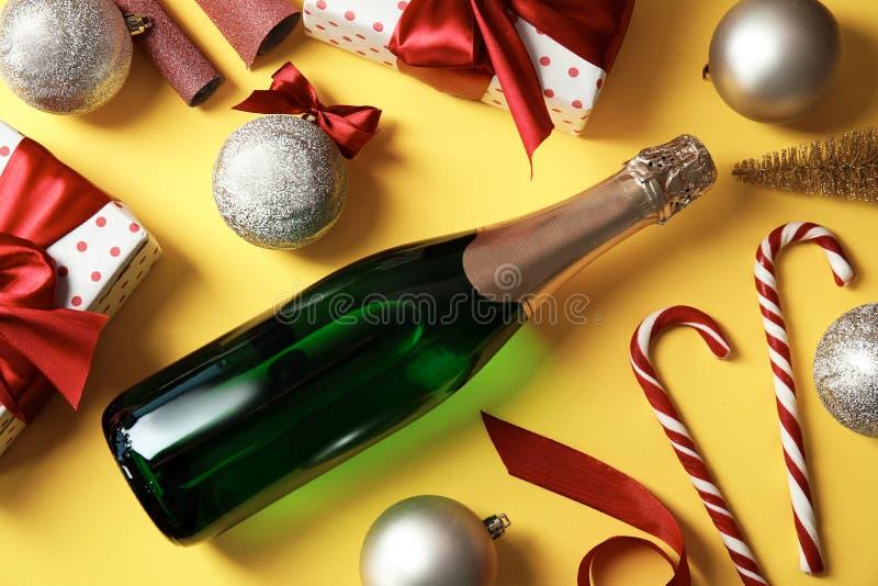 Composizione in Natale con la bottiglia di champagne e dei regali sul fondo di colore immagini stock