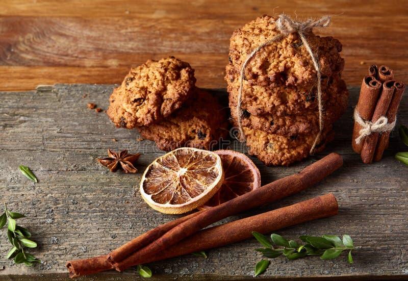 Composizione in Natale con la farina d'avena, i biscotti del cioccolato e le spezie, su fondo di legno, primo piano, fuoco selett fotografia stock