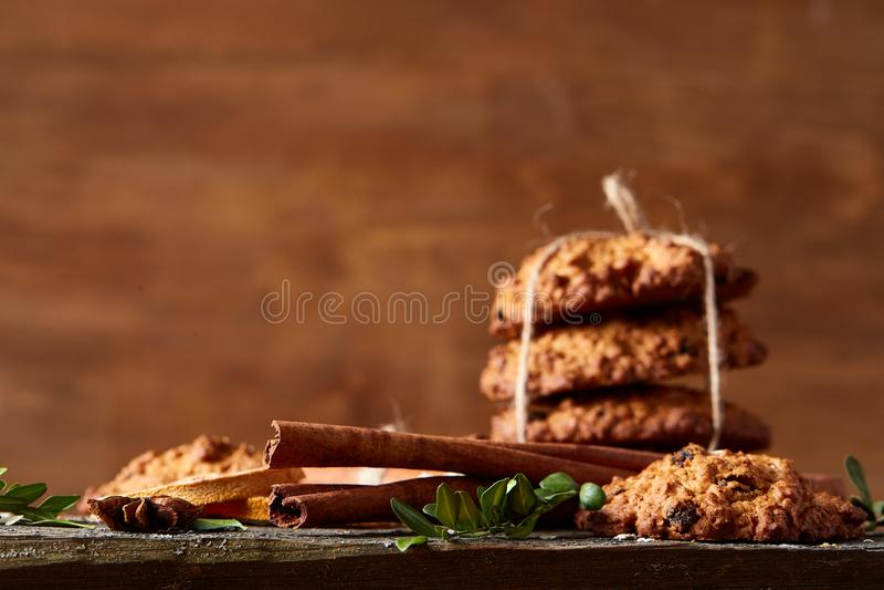 Composizione in Natale con la farina d'avena, i biscotti del cioccolato e le spezie, su fondo di legno, primo piano, fuoco selett fotografia stock libera da diritti