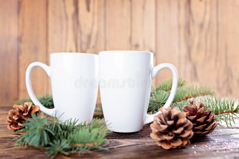 Composizione in Natale con le tazze bianche, coni dell'Natale-albero e fotografie stock libere da diritti