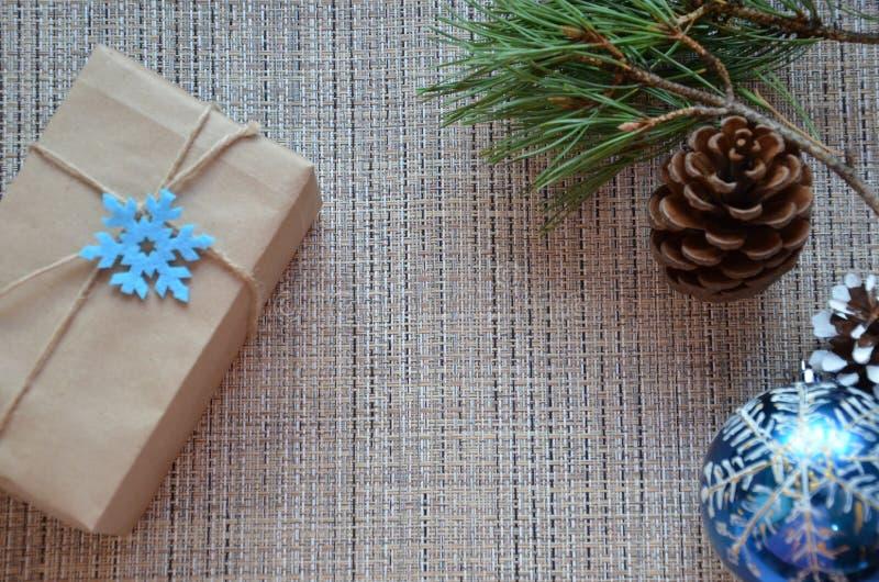 Composizione in natale Il regalo di Natale, la coperta tricottata, le pigne, abete si ramifica su fondo bianco di legno Disposizi fotografia stock libera da diritti