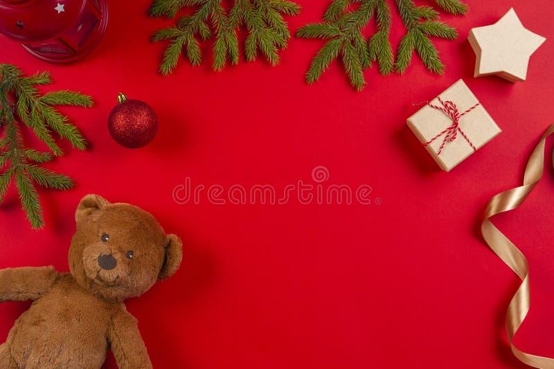Composizione in natale Orsacchiotto, rami di albero dell'abete, decorazioni di natale e contenitore di regalo attuale su fondo ro fotografia stock