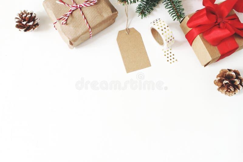 Composizione in natale Pagina dei rami di albero dell'abete, pigne, contenitori di regalo di natale, etichetta, nastro dorato di  fotografie stock