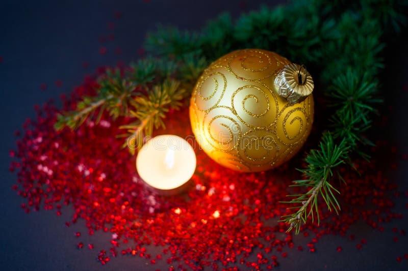 Composizione in Natale - palla dorata, ramo attillato e una candela bruciante fotografia stock libera da diritti