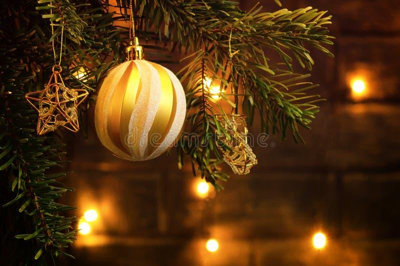 Composizione in Natale, palla ed altre decorazioni sui rami di un albero di Natale su un fondo scuro con le luci immagine stock libera da diritti