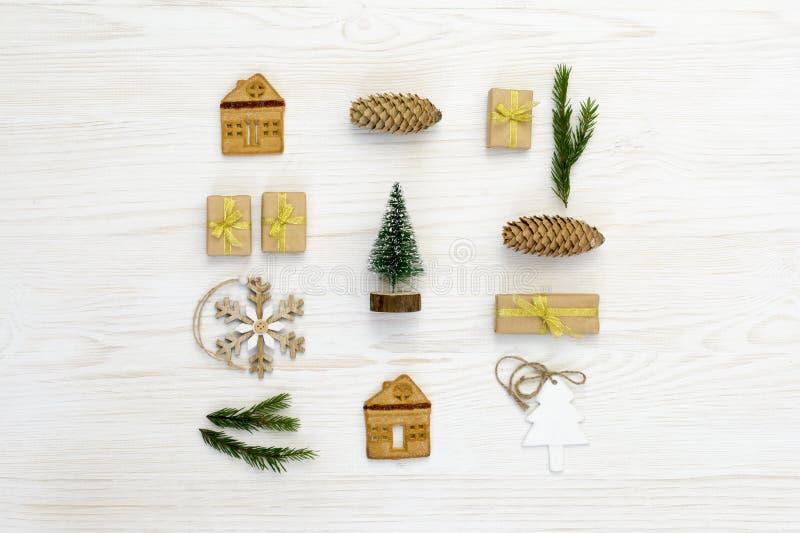 Composizione in natale Regali di Natale, pigna, decorazioni di legno su fondo bianco Disposizione piana, vista superiore fotografia stock libera da diritti