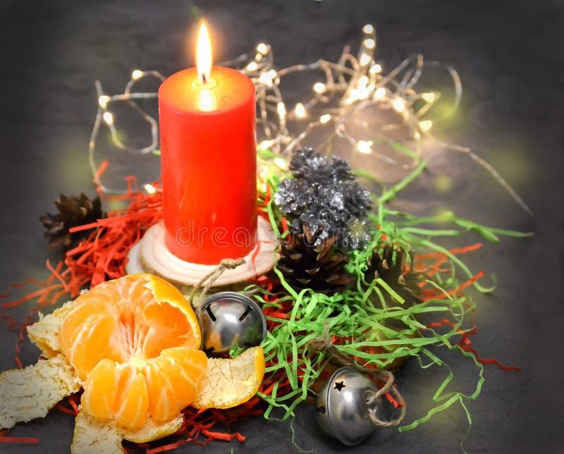 Composizione in Natale: una candela rossa che brucia su una tavola festiva su un fondo scuro Pan di zenzero, lamé, ghirlanda, man fotografia stock libera da diritti