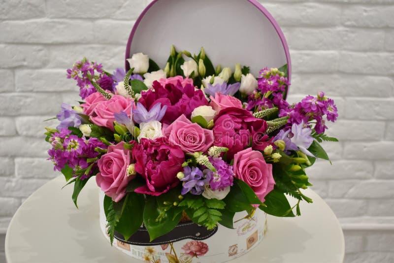 Composizione nel fiore in tronco originale Bei fiori in contenitore alla moda di cappello immagini stock libere da diritti