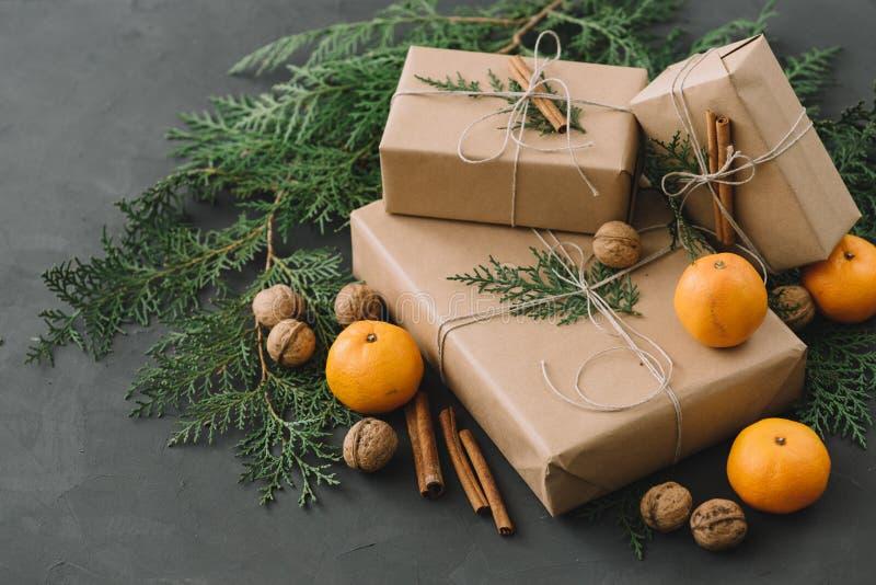 Composizione nel nuovo anno di Natale con i verdi delle pigne dei contenitori di mandarini nella decorazione nera di festa del fo immagini stock