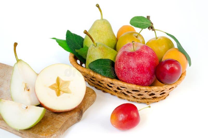Composizione nella frutta - un canestro di vimini di legno con gli interi frutti maturi - pere, prugne, albicocche e mele fotografia stock libera da diritti