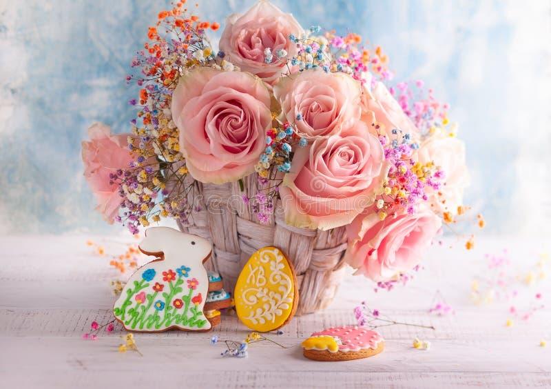 Composizione in Pasqua con i fiori ed i biscotti fotografia stock