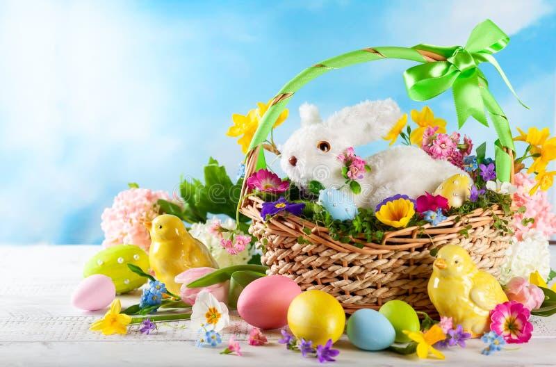 Composizione in Pasqua con la merce nel carrello del coniglietto, i fiori della molla e le uova di Pasqua variopinte fotografia stock libera da diritti