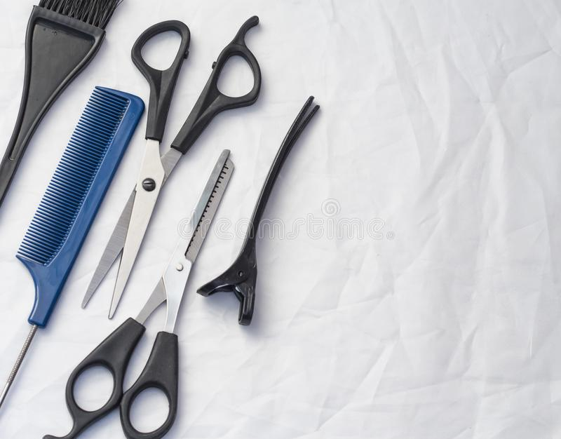 Composizione piana con gli strumenti professionali di lavoro di parrucchiere su fondo bianco, con lo spazio della copia fotografie stock