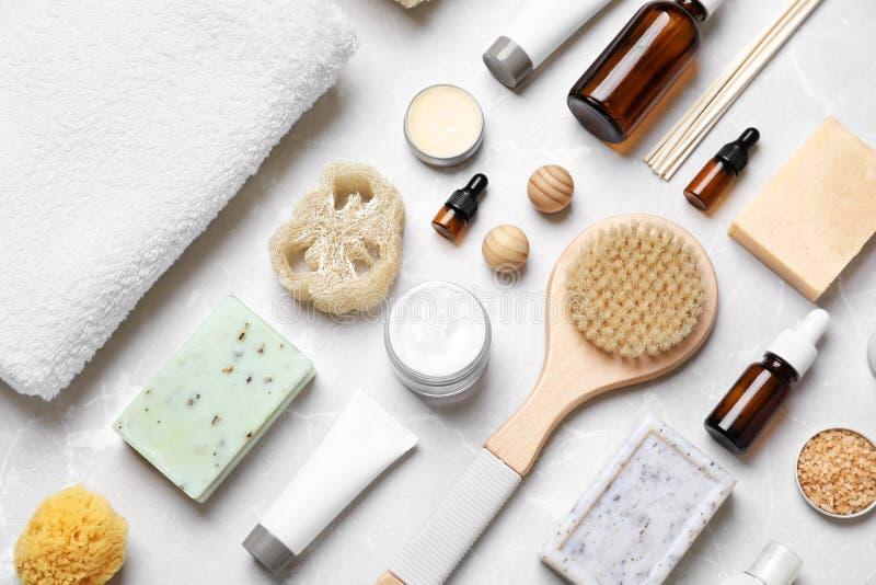 Composizione piana in disposizione con i cosmetici e l'asciugamano della stazione termale fotografia stock