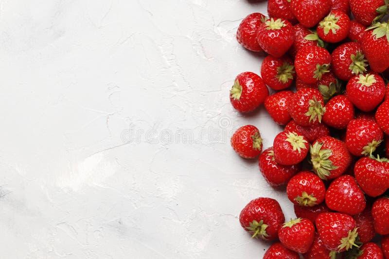 Composizione piana in disposizione con con le fragole mature saporite su fondo leggero fotografia stock