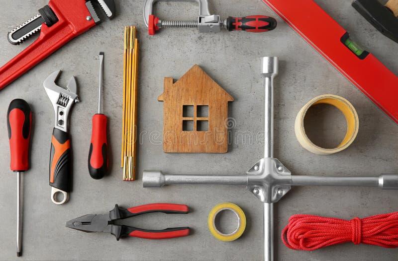 composizione piatta con figura a casa e utensili di riparazione sulla tavola di pietra fotografie stock libere da diritti