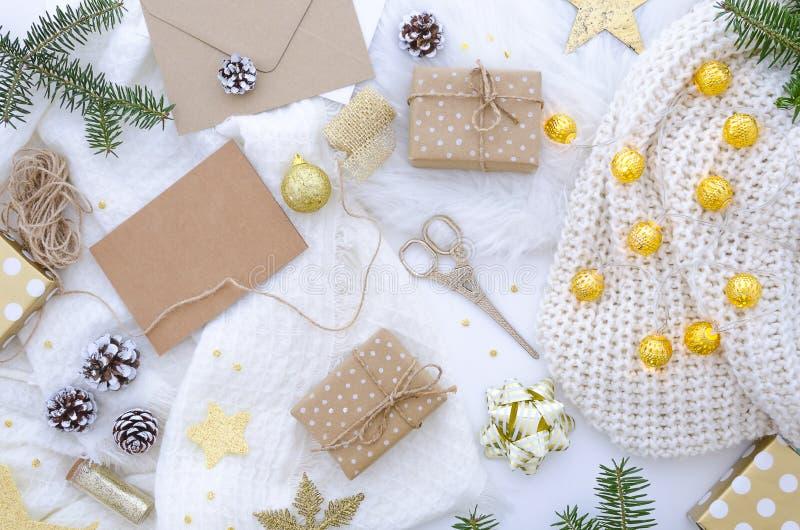 Composizione posta piana in chrismas con il contenitore di regalo fatto a mano e decorazione dorata fotografia stock libera da diritti