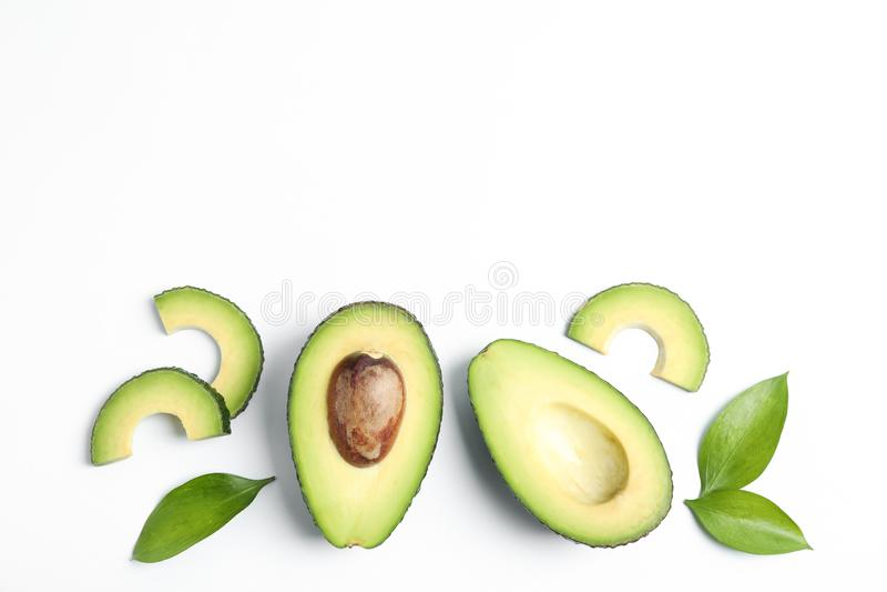 Composizione posta piana con gli avocado maturi su fondo bianco, spazio per testo fotografie stock
