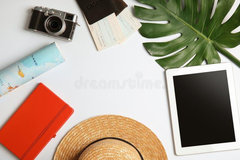 Composizione posta piana con gli oggetti turistici e computer su bianco, spazio della compressa per testo Agenzia di viaggi immagine stock