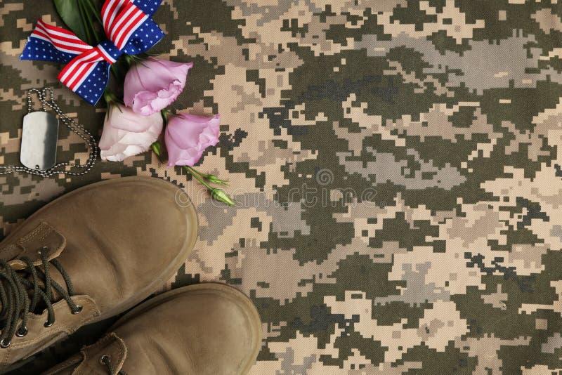 Composizione posta piana con gli stivali ed i fiori sul fondo del cammuffamento, spazio per testo Giorno di forze munite fotografie stock