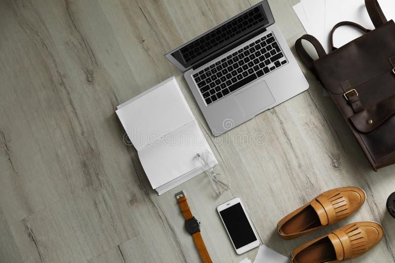 Composizione posta piana con il computer portatile ed il taccuino aperto sul pavimento di legno immagini stock