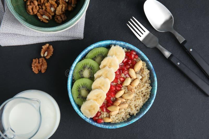 Composizione posta piana con il porridge ed il latte della quinoa sulla tavola nera immagine stock libera da diritti