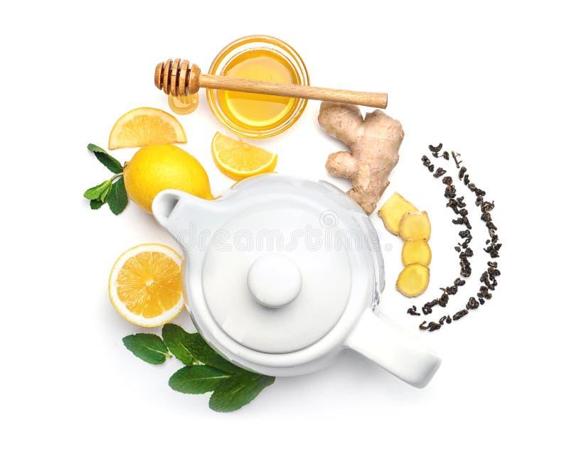 Composizione posta piana con la teiera, la menta, il limone, il miele e lo zenzero su fondo bianco fotografia stock