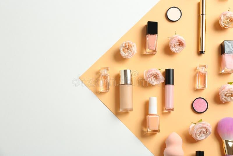 Composizione posta piana con le bottiglie di profumo, dei cosmetici e delle rose sul fondo di colore fotografie stock