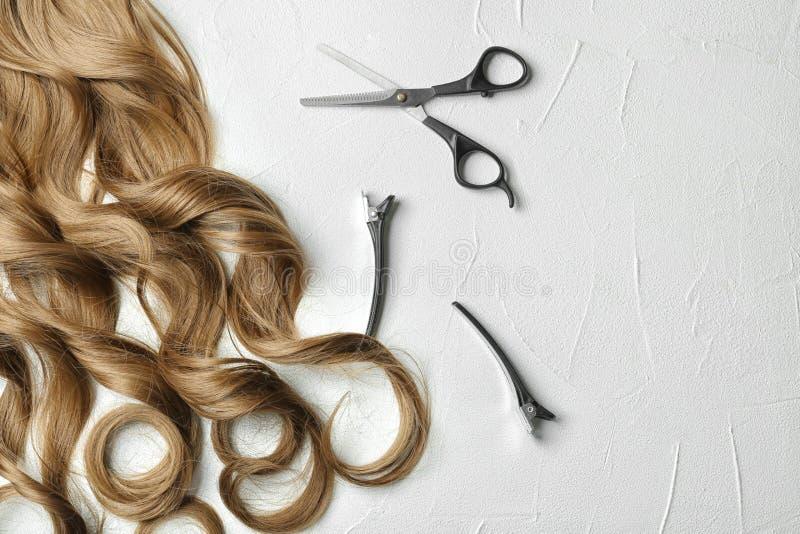 Composizione posta piana con le serrature e gli strumenti dei capelli ricci su fondo leggero fotografia stock libera da diritti