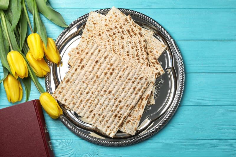 Composizione posta piana del pane azzimo, di Torah e dei fiori su fondo di legno immagine stock