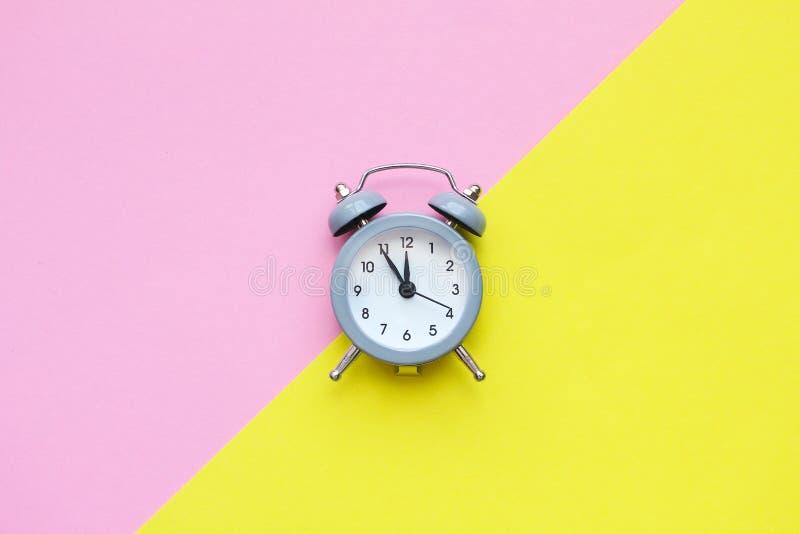 Composizione posta piana di mini sveglia grigia Spazio della copia, rosa e fondo giallo immagine stock
