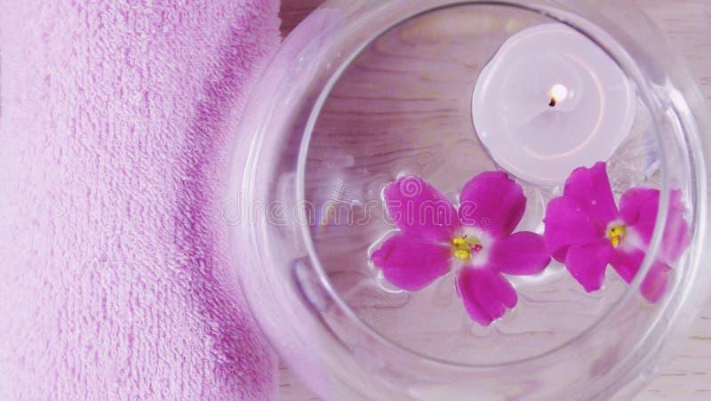 Composizione romantica con una candela ed i fiori viola che galleggiano in una ciotola di acqua fotografie stock libere da diritti