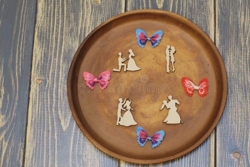 Composizione romantica sul piatto ceramico Figure di legno stilizzate degli amanti e delle farfalle ornamentali variopinte del ra fotografie stock libere da diritti