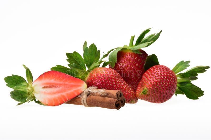 Composizione saporita delle bacche rosse mature della fragola con i petali ed i bastoni di cannella verdi fotografie stock libere da diritti